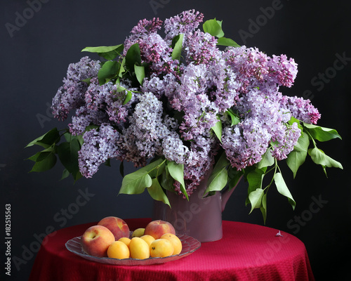 Purple lilac in the vase and fruit.