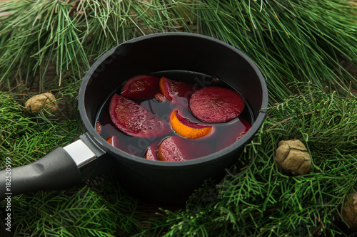 Hot mulled wine in a pot with handles and an iron kitchen scoop.