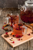 Hot autumn drink, fruit spicy tea with cranberry, cinnamon, anise. On a rustic old wooden table, with ingredients copy space - 182522557