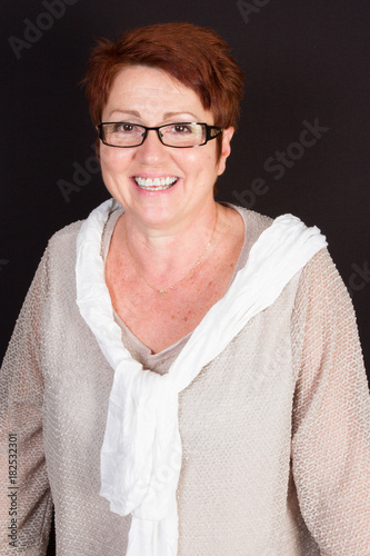 Portrait of a retired woman with short hair and glasses