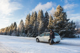 A man with a phone is standing by the car on a winter road - 182533543