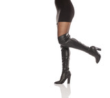 Pretty female legs in high leather boots and short dress