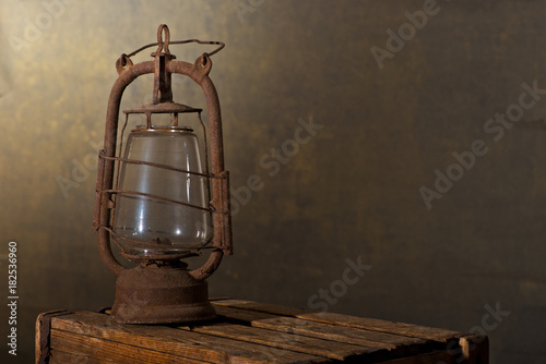 Fototapeta Old Rusty Lantern on the Wooden Desk in the Attic