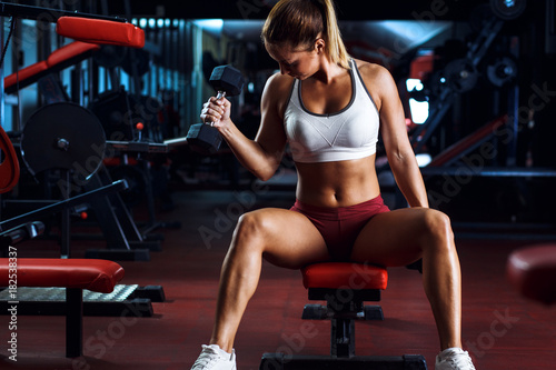 Fototapeta Young woman exercising with weight in the gym.