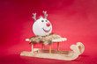 A reindeer bauble sitting on a sleigh, on the red background