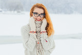 Beautiful smiling red head woman with glasses is wrapped in the scarf during the snowfall in the forest. Half-length horizontal portrait.