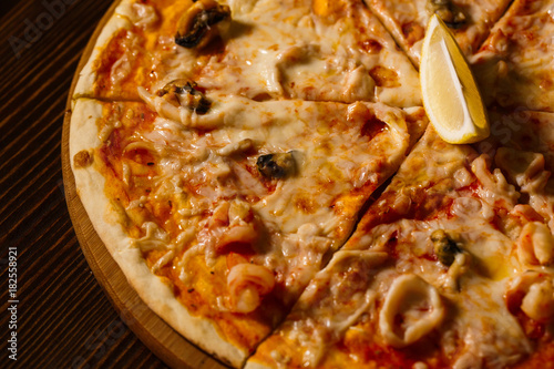 Hot pizza with melting cheese and seafood on a rustic wooden table Poster