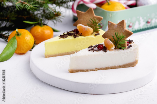 Fototapeta Christmas Dessert Two Slice of Cheesecakes Decorated with Citrus Gingerbread Star and Berries WoodenTray White Background Fir Branches Citrus