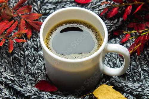 Mug of hot coffee in autumn setting on a wooden table with a knitted scarf, sweater. Comfort, warmth, cozy. © detry26