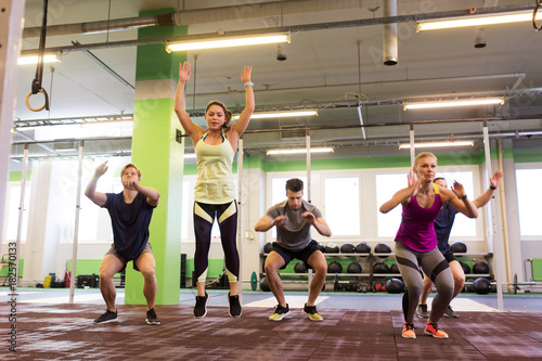 Plexiglas Fitness group of people exercising and jumping in gym