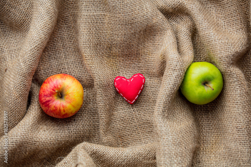 heart shape toy and apples on jute background