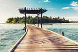 Wooden jetty with arch leading to a tropical island. Maldives