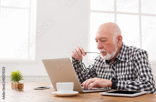 Mature man using laptop and writing in notepad