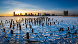 Sunset on the frozen Hudson River with old wood pilings and view on Downtown Jersey City, New Jersey - 182576905