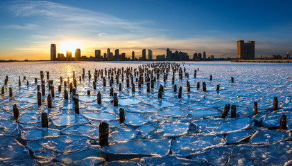Sunset on the frozen Hudson River with old wood pilings and view on Downtown Jersey City, New Jersey