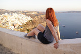 Woman looking at the town of Fira at sunset in Santorini island, Greece - 182582563