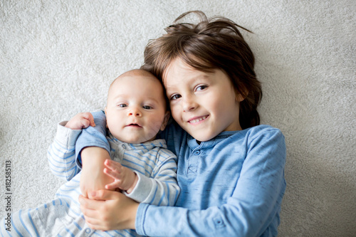 Papiers peints Kiev Happy brothers, baby and preschool children, hugging at home on white blanket