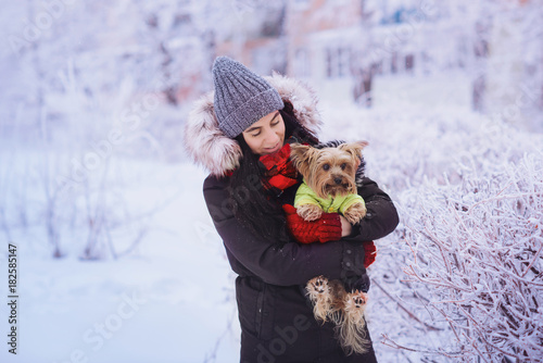 Attractive young woman having fun outside in snow with her dog Yorkshire Terrier. Young woman with a cute dog