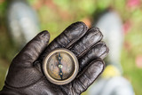 Man's hand in a leather glove holding a compass. Nature background. - 182587170