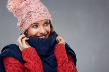 Close up face portrait of smiling woman wearing winter warm clothes.
