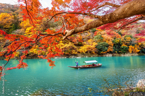 Fotobehang Kyoto Boatman punting the boat at river. Arashiyama in autumn season along the river in Kyoto, Japan.