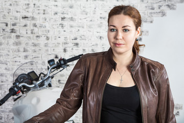 Attractive Caucasian woman motorcyclist portrait. Brown leather jacket and motorbike behind, indoor