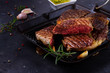 Grilled juisy beef steak in pan with spices on dark stone background