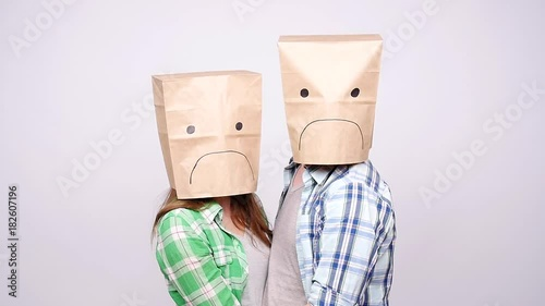 A couple with sad faces with paper bags on their heads