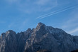 Two airplane contrails parallel to each other over the rugged peaks of the Julian Alps