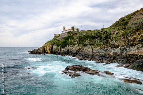Fotobehang Vuurtoren With a turquoise water in front the Lighthouse of Cudillero in Asturias is one of the most beautiful places in the North of Spain
