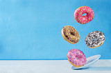 Flying multicolored donuts with plate - 182624570