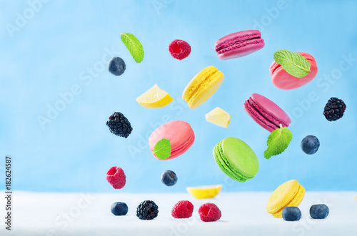 Foto op Aluminium Macarons Multicolored flying macaroni with berries and mint