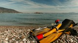 Snorkel equipment flippers and snorkeling mask tube lying on stone beach sea shore. Greece paralio Astros Peloponnese. Summer vacation swimming fun concept. Timelapse 4K - 182626785