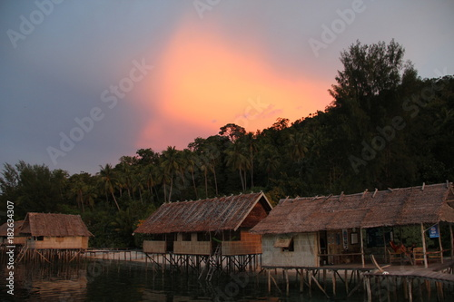 Foto op Plexiglas Grijs Beautiful Sunset with Ocean Over-Water Bungalows and Trees in Raja Ampat Indonesia