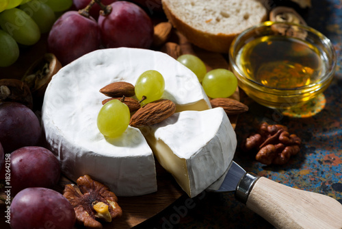 Fototapeta Camembert cheese, fruits and honey on a dark background