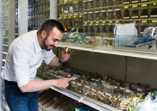 man picking metal tube extender in household shop