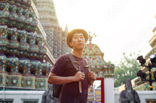 Poster Bangkok Young Asian traveling backpacker in Wat Pho with India inspired temple in Bangkok, Thailand
