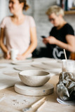Handmade ceramic bowl and two potters on blurred backgound - 182660108