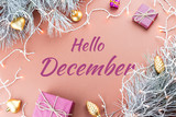 Hello December greeting card with fir tree, purple giftboxes, golden ornaments and Christmas lights in brown background - 182663393