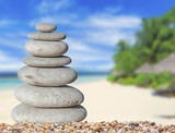 Small zen stone with beautiful sand and palm tree beach background for spa and balance symbol - 182663777