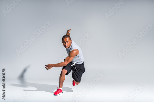 Sticker young african american sportsman running and looking at camera on grey