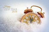 new year 2018 concept, vintage alarm clock in the snow shows five minutes before twelve, text - 182666541