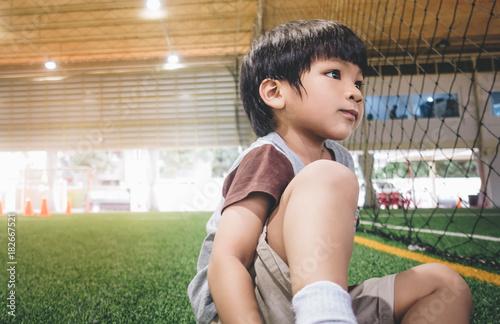 Plexiglas Voetbal Little boy sitting in soccer sport field