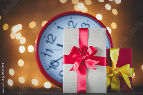 Christmas gifts and vintage alarm clock with Fairy Lights