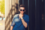 Handsome caucasian model dressed in trendy shirt and stylish sunglasses posing for camera while standing near wall for advertising fashion clothing content - 182680100