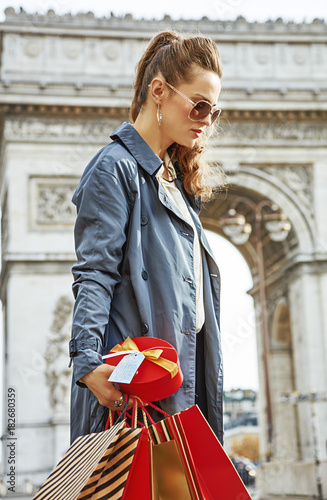 pensive modern woman with shopping bags in Paris, France Poster