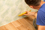 Man glues the wallpaper to the wall in the house - 182683386