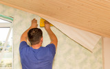 Man glues the wallpaper to the wall in the house - 182683394