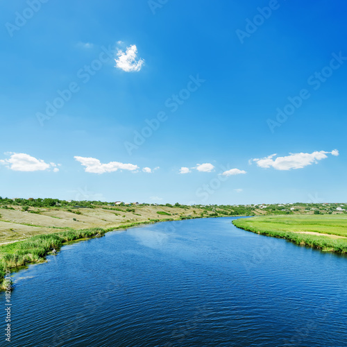 Tuinposter Blauw blue river in green landscape and sky with clouds over it