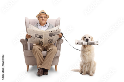 Mature man seated in an armchair holding a newspaper and a labrador retriever with a newspaper